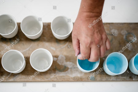 Staff worker Carsten Peters holds a mug during a glazing process at the Royal Porcelain Factory 'Koenigliche Porzellan-Manufaktur' (KPM) in Berlin, Germany, 26 July 2018. The name Royal Porcelain Factory 'Koenigliche Porzellan-Manufaktur' (KPM) exists since 1763, when King Frederick II of Prussia took over the company from a businessman. Nowadays the company is run by Berlin banker Joerg Woltmann.