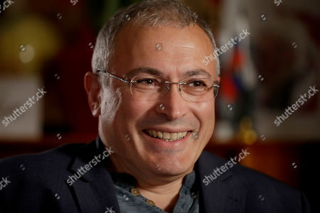 Russian opposition figure Mikhail Khodorkovsky, the former owner of the Yukos Oil Company, smiles during an interview by The Associated Press in London, . Khodorkovsky's London-based investigative unit, the Dossier Center, is compiling profiles of Russians it accuses of benefiting from corruption with an eye toward their eventual prosecution
