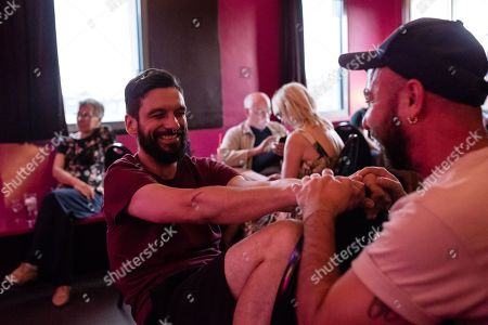 Stock Image of Two young men interact during the intermission of the drag performance of Joey Arias and Sherry Vine at the BKA (Berliner cabaret institution) in Berlin, Germany, 18 July 2018. (issued 27 July) Christopher Street Day (LGBT parade) in Berlin is held on Saturday, 28 July 2018 in Germany.