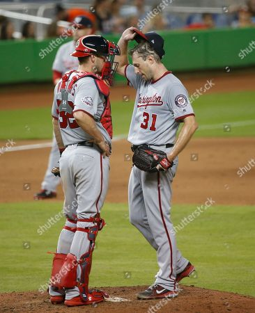 Stock Photo of Washington Nationals catcher Jamie Burke (32) talks with starting pitcher Max Scherzer (31) during the seventh inning of a baseball game against the Miami Marlins, in Miami. The Nationals defeated the Marlins 9-1
