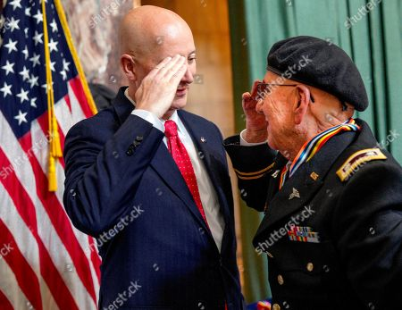 """Carl Lewis, Pete Ricketts. Neb. Gov. Pete Ricketts, left, returns a salute by Korean war veteran Lt. Col. Carl Lewis, of Kearney, Neb., during a ceremony on the 65th anniversary of the armistice, to honor veterans who served during the Korean War, in Lincoln, Neb., . President Donald Trump thanked North Korean leader Kim Jong Un on Friday for """"fulfilling a promise"""" to return the remains of U.S. soldiers missing from the Korean War, as a U.S. military plane made a rare trip into North Korea to retrieve 55 cases said to contain remains"""