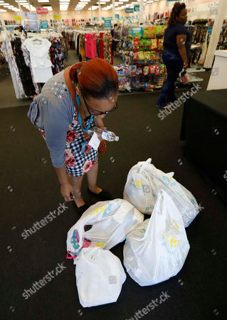LaToya Parker of Jackson, counts her bags of clothing she purchased for her grandchildren, in Jackson, Miss. Mississippi sales tax holiday is Friday and Saturday only and includes clothing and shoes that are $100 or below. School supplies and computers are not tax free this weekend. The 48-hour period gives shoppers an opportunity to save 7 percent on many clothing and shoes items