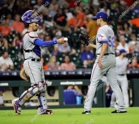 Stock Photo of Robinson Chirinos, Brandon Mann. Texas Rangers catcher Robinson Chirinos, left, hands relief pitcher Brandon Mann (52) the ball after the Rangers defeated the Houston Astros 11-2 in a baseball game, in Houston