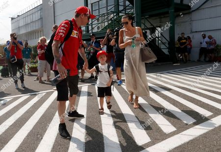Ferrari driver Kimi Raikkonen of Finland, left, walks through the paddock with his son Robin and wife Minttu Virtanen prior to the third free practice session for the Hungarian Formula One Grand Prix, at the Hungaroring racetrack in Mogyorod, northeast of Budapest, . The Hungarian Grand Prix will be held on Sunday