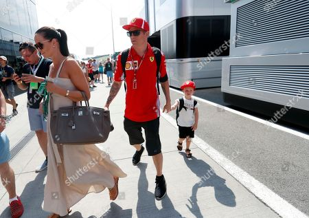 Ferrari driver Kimi Raikkonen of Finland, center, walks through the paddock with his son Robin and wife Minttu Virtanen prior to the third free practice session for the Hungarian Formula One Grand Prix, at the Hungaroring racetrack in Mogyorod, northeast of Budapest, . The Hungarian Grand Prix will be held on Sunday