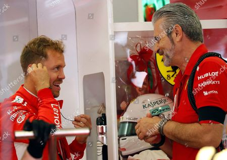 Ferrari driver Sebastian Vettel of Germany, left, speaks with Ferrari team principal Maurizio Arrivabene wears black armband, after the death of former Ferrari president Sergio Marchionne, during the third free practice session for the Hungarian Formula One Grand Prix, at the Hungaroring racetrack in Mogyorod, northeast of Budapest, . The Hungarian Grand Prix will be held on Sunday