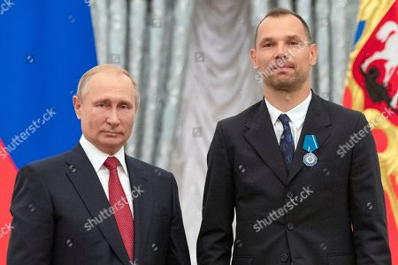 Russian President Vladimir Putin, left, and Russia's soccer team player Sergei Ignashevich pose during the State Prize awards ceremony in Kremlin in Moscow, Russia, . Russia's soccer team players and stuff were awarded by State Prizes and honorary diplomas as Russia's soccer team reach the quarterfinals at the World Cup 2018