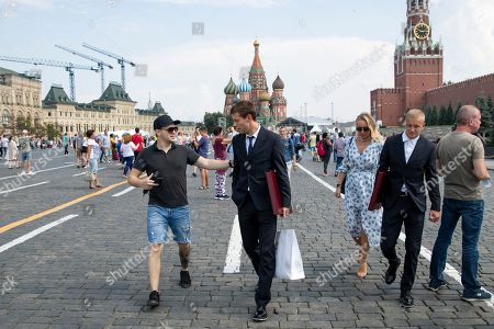 Russia's soccer team player Fyodor Smolov, center, is approached by a passer in Red Square, with the Saint Basil's Cathedral, center, and Spasskaya Tower, right, in the background, after the State Prize awards ceremony in Kremlin, in Moscow, Russia, . Russia's soccer team players and staff were awarded by State Prizes and honorary diplomas as Russia's soccer team reach the quarterfinals at the World Cup 2018