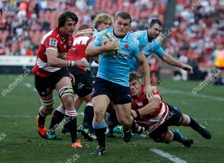 Waratahs' Tom Robertson, front, breaks away from the Lions' defenders to score a try during the Super Rugby semifinal match between Lions and Waratahs at Ellis Park stadium in Johannesburg, South Africa