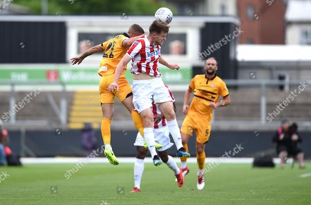 Tyler Forbes of Newport County and Cameron Mcjannet of Stoke City U23s compete for the ball.