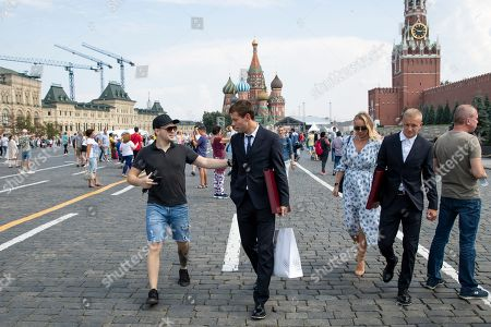 Russia's soccer team player Fyodor Smolov, (C), is recognized by a passer in Red Square, with the Saint Basil's Cathedral, center, and Spasskaya Tower, right, in the background, after the State Prize awards ceremony in Kremlin, in Moscow, Russia, 28 July 2018. Russia's soccer team players and staff were awarded by State Prizes and honorary diplomas as Russia's soccer team reached the quarterfinals at the World Cup 2018.