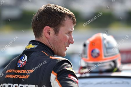 Kasey Kahne stands on pit road during qualifying for Sunday's NASCAR Cup Series auto race, in Long Pond, Pa