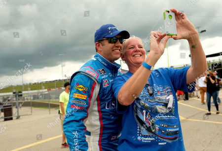 Elliott Sadler stops to pose for a selfie with a fan after winning the pole for the NASCAR Xfinity Series auto race, at Iowa Speedway in Newton, Iowa