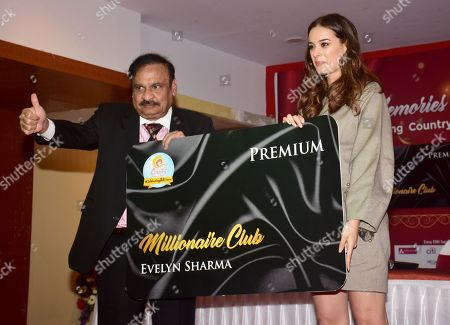 Indian film actress Evelyn sharma seen holding a large format of the new card with the president of the club as she launch the CountryClubs Millionaire Club card in Mumbai.