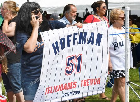 Trevor Hoffman fan Rocio Hodges, of Chula Vista, Calif., uses a banner to find her husband before the start of National Baseball Hall of Fame induction ceremonies, in Cooperstown, N.Y