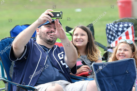Trevor Hoffman fan Chris Kerner, left, of Reistertown, Md., takes a selfie with his daughters Abby Kerner, center, and Maddie Kerner before induction ceremonies at the National Baseball Hall of Fame in Cooperstown, N.Y