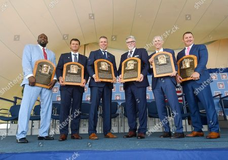 Baseball Hall of Famers from left, Vladimir Guerrero, Trevor Hoffman, Chipper Jones, Jack Morris, Alan Trammell, and Jim Thome, hold their plaques after an induction ceremony at the Clark Sports Center, in Cooperstown, N.Y