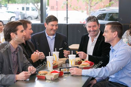 To celebrate the 50th anniversary of the Big Mac, McDonald's CEO Steve Easterbrook, fourth left, and McDonald's franchisees Nick, Dan, Mike and Tony Delligatti, grandsons and son of the late inventor of the Big Mac, Jim Delligatti, enjoy a lunch of Big Mac sandwiches while admiring the MacCoin at McDonald's global restaurant in Chicago on . Starting Thursday, August 2, 2018, Big Mac fans in more than 50 participating countries can get their hands on the MacCoin. Customers can share, collect and redeem the MacCoin for a free Big Mac at participating restaurants worldwide through 2018