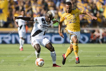 Tigres' Rafael de Souza (R) vies for the ball with Leonel Castillo (L) of Tijuana's Xolos during a second round match of the Apertura Tournament 2018, at the Universitario stadium, in Monterrey, Mexico, 29 July 2018.