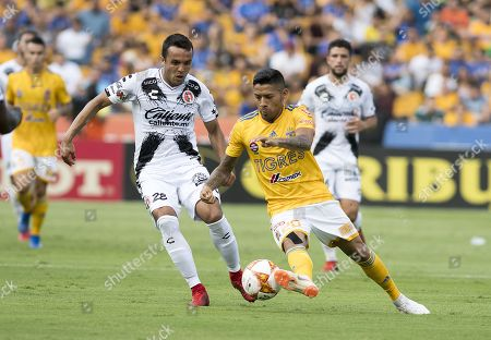Omar Mendoza (L) of Tijuana's Xolos vies for the ball with Tigres' Javier Aquino (R) during a second round match of the Apertura Tournament 2018, at the Universitario stadium, in Monterrey, Mexico, 29 July 2018.