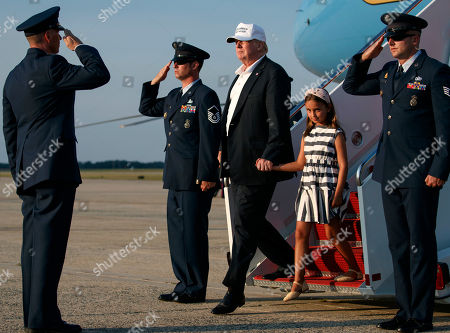Donald Trump, Arabella Kushner, Melania Trump, and Barron Trump. President Donald Trump, holding the hand of his granddaughter Arabella Kushner, arrives on Air Force One, in Andrews Air Force Base, Md., en route to Washington as they return from Trump National Golf Club in Bedminster, N.J