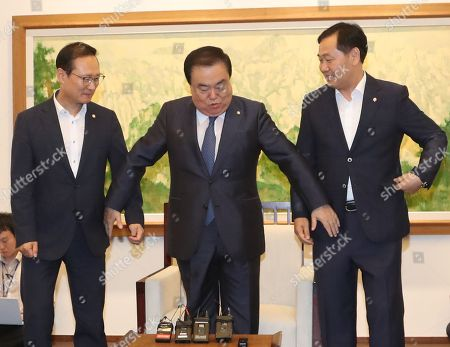 Parliament Speaker Moon Hee-sang (C) reaches out to hold hands with ruling and opposition party floor leaders for a photo session at the National Assembly in Seoul ahead of their meeting in Seoul, South Korea, 30 July 2018. Moon and the floor leaders -- Hong Young-pyo of the ruling Democratic Party (L) and Kim Kwan-young of the minor opposition Bareunmirae Party -- discussed holding an extra parliament session in August to handle delayed bills. Kim Sung-tae of the main opposition Liberty Korea Party did not show up, citing party affairs.