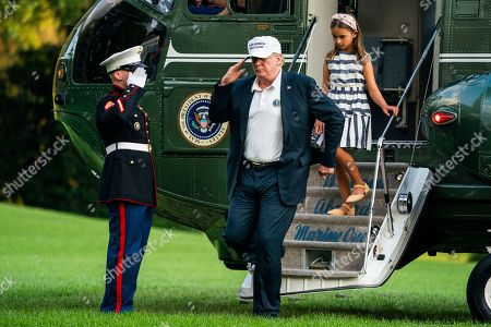 U.S. President Donald Trump (L) and his granddaughter Arabella Rose Kushner (R) walk off Marine One as they return from a weekend stay in Bedminster, New Jersey at the White House in Washington, DC