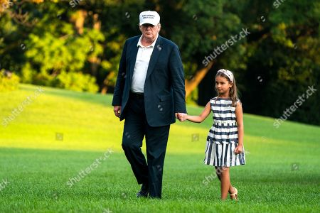 U.S. President Donald Trump (L) and his granddaughter Arabella Rose Kushner (R) walk across the South Lawn as they return from a weekend stay in Bedminster, New Jersey at the White House in Washington, DC