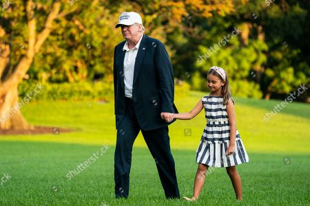 U.S. President Donald J. Trump (L) and his granddaughter Arabella Rose Kushner (R) walk across the South Lawn as they return from a weekend stay in Bedminster, New Jersey at the White House in Washington, DC