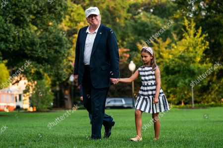 Stock Picture of U.S. President Donald J. Trump (L) and his granddaughter Arabella Rose Kushner (R) walk across the South Lawn as they return from a weekend stay in Bedminster, New Jersey at the White House in Washington, DC
