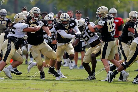 Stock Image of New Orleans Saints running back Shane Vereen runs through a hole as center Max Unger, left, blocks defensive tackle Tyeler Davison, and wide receiver Dan Arnold (85) blocks linebacker Demario Davis (56) during training camp at their NFL football training facility in Metairie, La