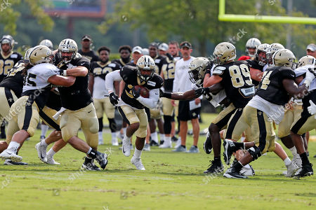 Stock Picture of New Orleans Saints running back Shane Vereen runs through a hole as center Max Unger, left, blocks defensive tackle Tyeler Davison, during training camp at their NFL football training facility in Metairie, La