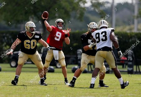 New Orleans Saints quarterback Drew Brees (9) passes as center Max Unger (60) and offensive lineman John Fullington block defensive tackle David Onyemata (93) during training camp at their NFL football training facility in Metairie, La
