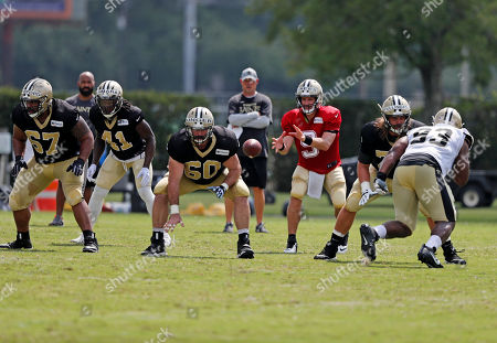 New Orleans Saints center Max Unger (60) hikes the ball to quarterback Drew Brees (9) as guard Larry Warford (67), running back Alvin Kamara (41) and offensive lineman John Fullington line up against defensive tackle David Onyemata (93) during training camp at their NFL football training facility in Metairie, La