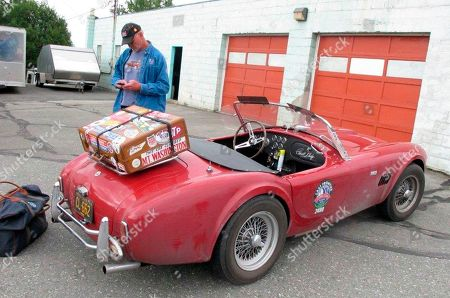 Stock Picture of Tom Cotter stands near his red Shelby Cobra, in Anchorage, Alaska. The classic convertible was damaged when a bear broke into it last week while Cotter was touring the state with a group of friends also driving classic Shelby Cobras