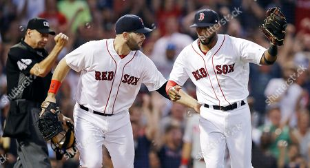 Eduardo Nunez, Mitch Moreland, Andy Fletcher. Boston Red Sox second baseman Eduardo Nunez, right, is congratulated by first baseman Mitch Moreland, center, after tagging out Philadelphia Phillies' Rhys Hoskins while covering home plate to during the third inning of a baseball game at Fenway Park in Boston, . At left making the call is umpire Andy Fletcher