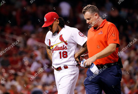 St. Louis Cardinals trainer Chris Conroy, right, talks with starting pitcher Carlos Martinez as Martinez leaves a baseball game against the Colorado Rockies during the fifth inning, in St. Louis