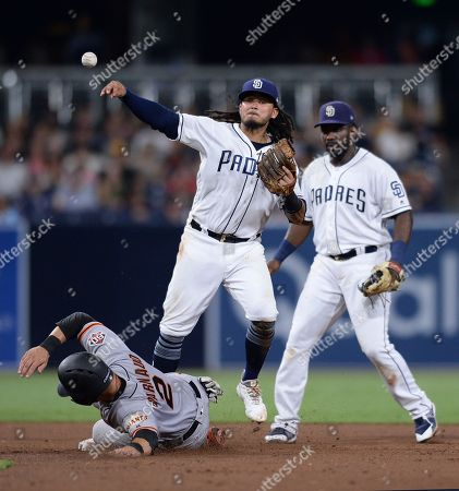San Francisco Giants' Chase d'Arnaud is forced out at second base by San Diego Padres shortstop Freddy Galvis, center, on a ball hit by Steven Duggar during the sixth inning of a baseball game, in San Diego