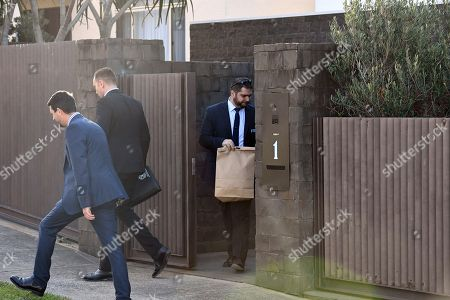 NSW Police detectives hold an evidence bag as they leave the house of Kings Cross nightclub owner John Ibrahim during a police operation at Dover Heights in Sydney, Australia, 31 July 2018. Police said the operation was conducted in connection with serving of a firearms prohibition order.