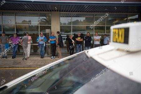 Taxi drivers stand outside their vehicles as they join a countrywide protest outside the Seve Ballesteros Airport in Santander, northern Spain, 31 July 2018. Taxi drivers in several Spanish cities have joined colleagues in Barcelona, who started the protests last 25 July, to show their support for a taxi strike in defense of the regulation which provides one local license for VTC (Tourism Vehicles with Driver) vehicle, from companies like Uber or Cabify, out of each 30 licenses for taxis.