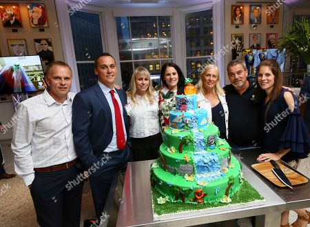 The Nelson family, from left, Travis Nelson, Todd Nelson Jr., Natasha Lucke, Alissa Gander, Shari Nelson, Todd Nelson, and Ashley Nelson, before a cake cutting ceremony after Kalahari Resorts & Conventions, announced a national partnership with Macy's Thanksgiving Day Parade, in New York. The company will debut a new larger-than-life float this November