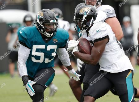 Blair Brown, Leonard Fournette. Jacksonville Jaguars linebacker Blair Brown (53) defends against running back Leonard Fournette, right, during a practice at NFL football training camp, in Jacksonville, Fla