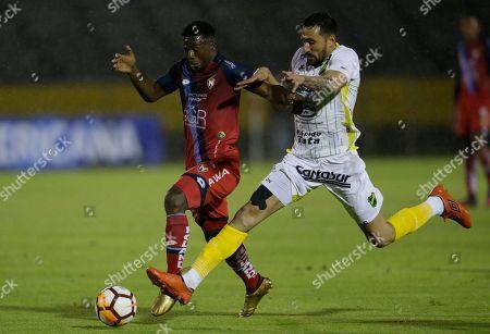 Alejandro Villalva of Ecuador's El Nacional, left, fights for the ball with Jonas Gutierrez of Argentina's Defensa y Justicia during a Copa Sudamericana soccer game in Quito, Ecuador
