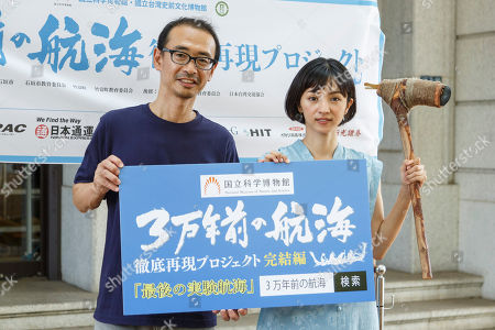 Stock Photo of Japanese actress and singer Hikari Mitsushima (R) holding a stone axe poses for the cameras during a news conference at the National Museum of Nature and Science in Tokyo. The museum aims to collect 30 million yen to recreate the Japanese ancestors' journey between Taiwan and Yonaguni Island on a wooden dugout canoe.