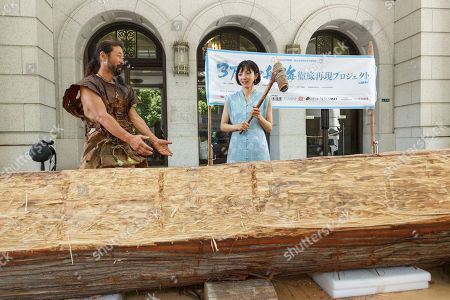 Japanese actress and singer Hikari Mitsushima (C) holds a stone axe during a news conference at the National Museum of Nature and Science in Tokyo. The museum aims to collect 30 million yen to recreate the Japanese ancestors' journey between Taiwan and Yonaguni Island on a wooden dugout canoe.