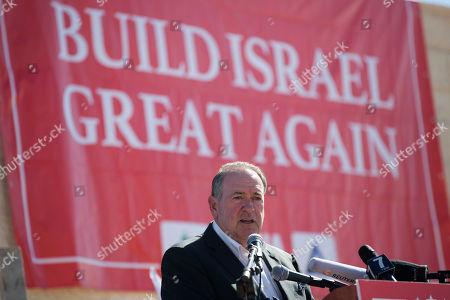 U.S. Governor Mike Huckabee speaks to the media prior to laying a brick at a new housing complex in the West Bank settlement of Efrat