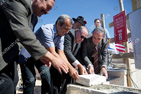 U.S. Governor Mike Huckabee, 2nd right, lays a brick at a new housing complex in the West Bank settlement of Efrat
