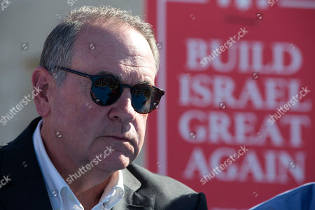 U.S. Governor Mike Huckabee takes questions from the media, prior to laying a brick at a new housing complex in the West Bank settlement of Efrat