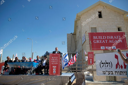 U.S. Governor Mike Huckabee, centre, speaks to the media prior to laying a brick at a new housing complex in the West Bank settlement of Efrat