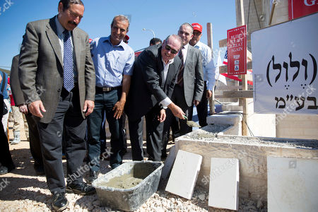 U.S. Governor Mike Huckabee, centre right, lays a brick at a new housing complex in the West Bank settlement of Efrat